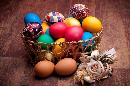 Basket with colorful Easter eggs on wood table. photo