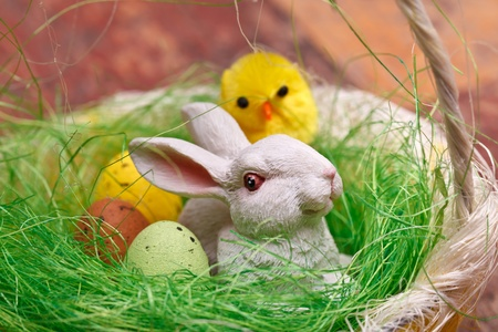 Easter basket with candy eggs, bunny and chicken. photo