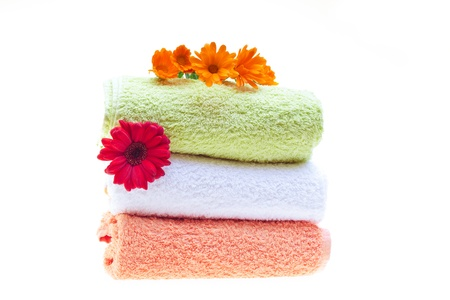 Pile of clean towels decorated with red gerbera and calendula flowers, isolated on white background. photo