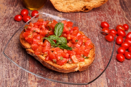 Traditional Italian Recipes - Apulian bread rings (friselle) with fresh chopped tomatoes, basil and olive oil. photo