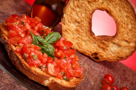 Traditional Italian Recipes - Apulian bread rings (friselle) with fresh chopped tomatoes, basil and olive oil. Stock Photo - 13354455