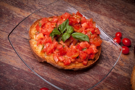 Traditional Italian Recipes - Bread ring(frisella) with fresh chopped tomatoes, basil and olive oil.