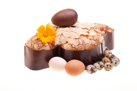 Traditional Italian desserts for Easter - Easter dove decorated with raw chicken and quail eggs, with a chocolate egg on the top, isolated on white background. photo