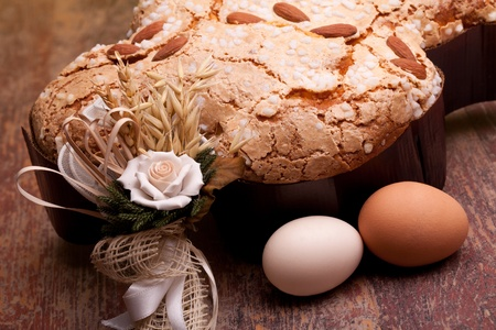 Traditional Italian desserts for Easter - Closeup of Easter dove and eggs, on wood table. Stock Photo