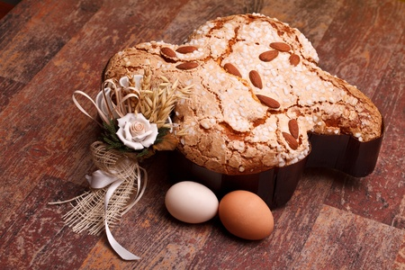 Traditional Italian desserts for Easter - Easter dove and eggs, on wood table.
