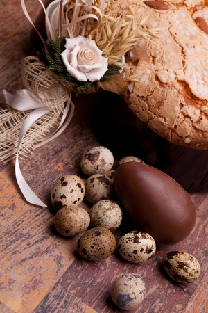 Easter still life with quail eggs, chocolate egg  and Easter dove on wood table. Stock Photo - 13354473