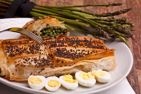 Mediterranean cuisine recipes - Asparagus in crust with poppy seeds on top and quail eggs. photo