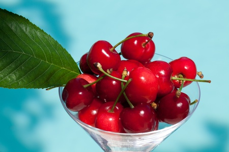 Fruits - Glass with fresh ripe cherries on blue water background  photo