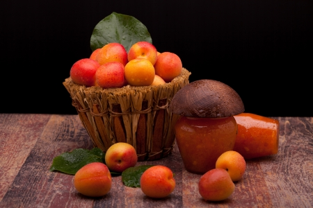 Fruits and their preservation - Basket with fresh apricots and jars with homemade apricot jam  photo