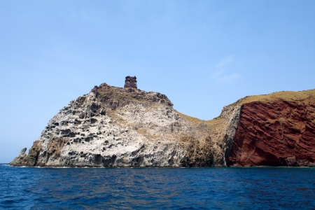 capraia: Volcanic formations and ancient tower on the top, Capraia Island, Tuscan Archipelago, Italy.