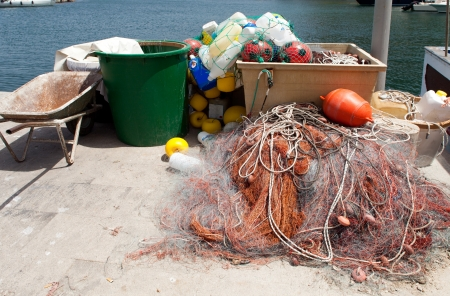 capraia: Fish nets and various plastic recipients used by the fishermen like floaters helping to point the nets in the sea  Pier of fishermen boats at Capraia Island, Italy  Stock Photo