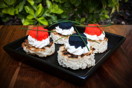 Finger Food - Red and black caviar canap�s decorated with chives  photo