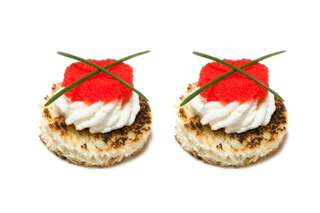Finger Food - Red and black caviar canap�s decorated with chives, on white background  photo