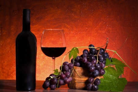 Still life with red wine and grapes on warm background.