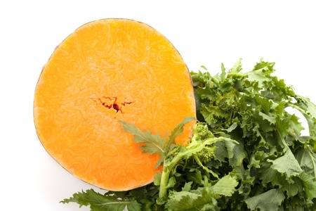Slice of buttercup squash and bunch of broccoli rabe on white background  Stock Photo - 17780148