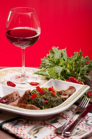 Famous traditional Italian plate made with   broccoli rabe and sausages, accompanied by a glass of red wine  photo