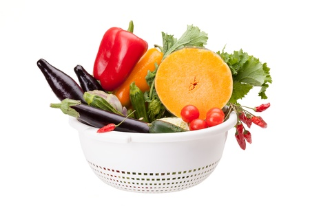 Colander with mix of vegetables isolated on white background  photo