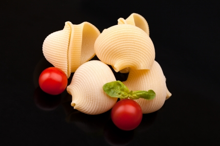 cherry varieties: Pasta Varieties - Lumaconi with cherry tomatoes and basil over black background