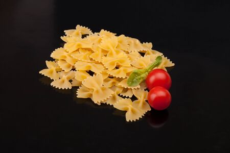 cherry varieties: Pasta Varieties - Farfalle with cherry tomatoes and basil over black  background