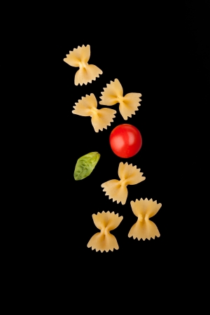 cherry varieties: Pasta Varieties - Farfalle pasta, cherry tomato and basil leaf, isolated on black  background
