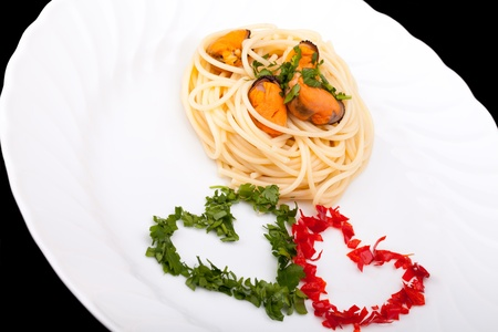 Italian Cuisine - First Courses - Pasta - Spaghetti with mussels decorated with hearts of parsley and chili pepper in order to have to colors of Italian flag  photo