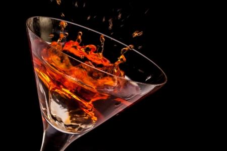 Closeup of glass with splashing spritz on black background  Stok Fotoğraf