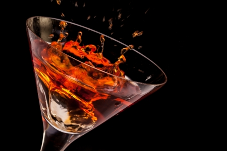 Closeup of glass with splashing spritz on black background  Stock Photo