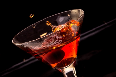 Red splashing cocktail glass with cherry in black ambient light.