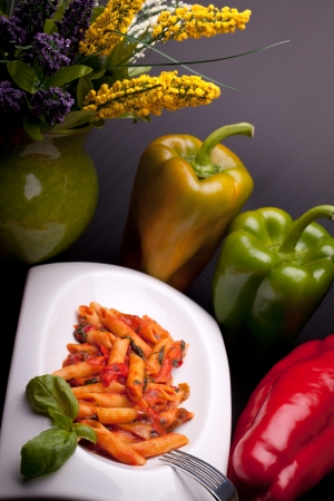 Italian typical recipes - Penne rigate with peppers sauce, decorated with fresh peppers and pitcher with flowers  photo