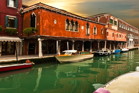 atmosphere construction: Ancient buildings along channel in Murano, Italy at sunset