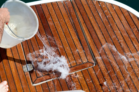 Washing the deck with water throwed from a plastic buket