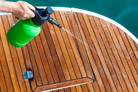 Spraying cleaning solution on deck of boat