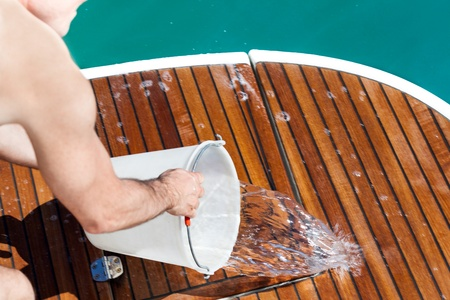 boat deck: Man washing the deck of a boat