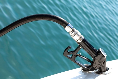Closeup of Diesel pump nozzle refilling boat tank  photo