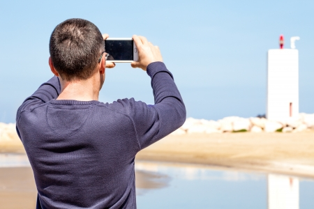 Man taking pictures of beach with the smartphone. Archivio Fotografico