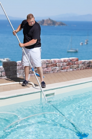 Photo of man cleaning a swimming pool situated above the sea, with island in the background  Stock Photo