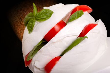 Mozzarella cheese sliced and filled with cherry tomatoes and basil. photo