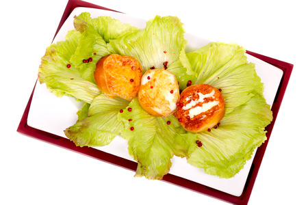 scamorza cheese: Italian Cuisine - Plate with grilled slices of scamorza cheese, on lettuce bed. Stock Photo