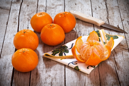Honey tangerines whole and one peeled, on antique wooden table. Standard-Bild