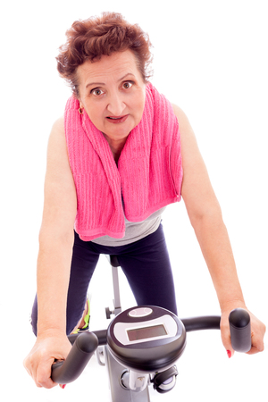 Senior woman making exercise on medical bike. photo