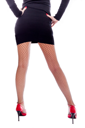 Long sexy legs in fishnet stockings and red high heels shoes  Stock Photo