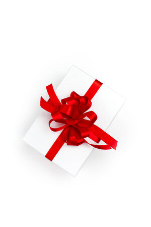 overhead shot: Overhead shot of white pack with present decorated with red satin bow, on white . Stock Photo