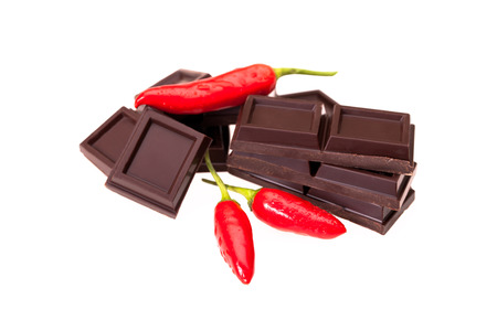 Red chilli peppers and pieces of chocolate isolated on white . Archivio Fotografico