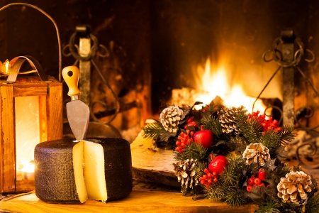 Christmas food from Italy; typical seasoned cheese from Pienza in front of country fireplace.