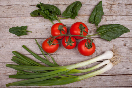 overhead shot: Vegetarian cuisine ingredients: green onions, tomatoes, spinach leaves. Overhead shot. Stock Photo