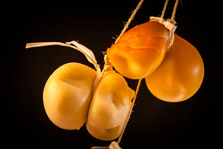 scamorza cheese: Two pieces of scamorza cheese hanged over black background. Stock Photo