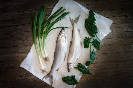 Raw foods - European whitefish (Coregonus lavaretus) with fresh green onions and spinach leaves.