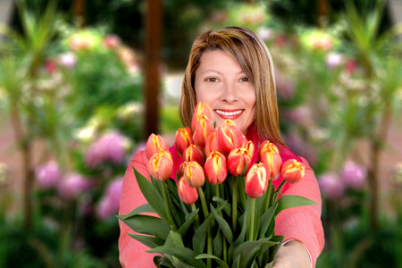 Portrait of smiling middle-aged woman holding a bunch of tulips  photo