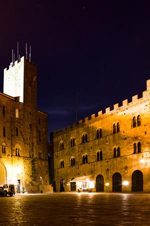 priori: Volterra, Toscana, Italia - Piazza Dei Priori di notte con il Palazzo Pretorio e Torre del Porcellino nel lato sinistro e il Palazzo Vescovile sul lato destro.