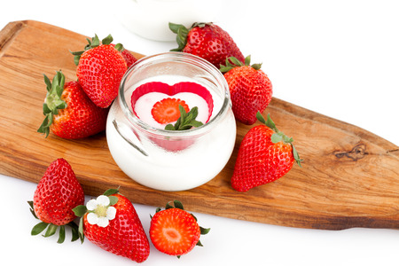 Jar with yogurt decorated with fresh strawberries. photo
